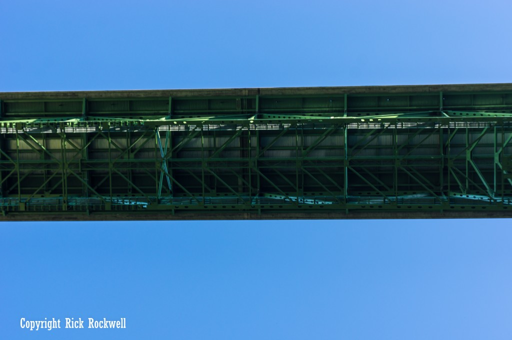 Directly underneath the bridge.